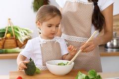 Famille heureuse dans la cuisine Fille de mère et d'enfant faisant cuire breakfest savoureux de la salade fraîche Petit découpage Images stock