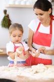Famille heureuse dans la cuisine Fille de mère et d'enfant faisant cuire le tarte ou les biscuits de vacances pour le jour de mèr Photo stock
