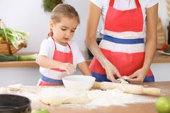 Famille heureuse dans la cuisine Fille de mère et d'enfant faisant cuire le tarte ou les biscuits de vacances pour le jour de mèr Image stock