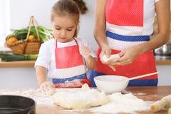 Famille heureuse dans la cuisine Fille de mère et d'enfant faisant cuire le tarte ou les biscuits de vacances pour le jour de mèr Photos libres de droits