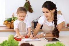 Famille heureuse dans la cuisine La fille de mère et d'enfant font le menue pour faire cuire breakfest savoureux dans la cuisine  Images stock