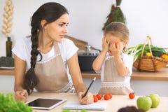 Famille heureuse dans la cuisine La fille de mère et d'enfant font le menue pour faire cuire breakfest savoureux dans la cuisine  Photo libre de droits