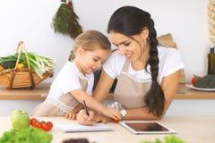 Famille heureuse dans la cuisine La fille de mère et d'enfant font le menue pour faire cuire breakfest savoureux dans la cuisine  Photos stock