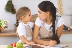 Famille heureuse dans la cuisine La fille de mère et d'enfant font le menue pour faire cuire breakfest savoureux dans la cuisine  Image libre de droits