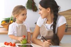 Famille heureuse dans la cuisine La fille de mère et d'enfant font le menue pour faire cuire breakfest savoureux dans la cuisine  Image stock