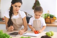 Famille heureuse dans la cuisine La fille de mère et d'enfant font le menue pour faire cuire breakfest savoureux dans la cuisine  Photos libres de droits