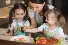 Famille heureuse dans la cuisine Maman et filles jouant et ayant l'amusement dans la préparation de cuisine Image libre de droits