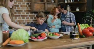 Famille heureuse dans la cuisine, parents regardant des enfants faisant cuire la nourriture coupant ensemble des légumes banque de vidéos