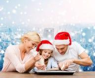 Famille heureuse dans la cuisson de chapeaux d'aide de Santa Image stock