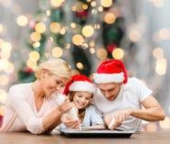 Famille heureuse dans la cuisson de chapeaux d'aide de Santa Images stock