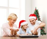 Famille heureuse dans la cuisson de chapeaux d'aide de Santa Photographie stock libre de droits