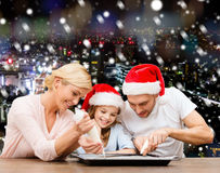 Famille heureuse dans la cuisson de chapeaux d'aide de Santa Photos stock