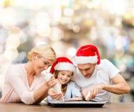 Famille heureuse dans la cuisson de chapeaux d'aide de Santa Photographie stock