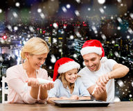 Famille heureuse dans la cuisson de chapeaux d'aide de Santa Photo libre de droits
