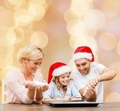 Famille heureuse dans la cuisson de chapeaux d'aide de Santa Photos libres de droits