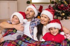 Famille heureuse dans le chapeau de Santa étreignant sous la couverture Photographie stock