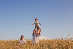 Famille heureuse dans le domaine de céréale au coucher du soleil Photo libre de droits