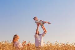 Famille heureuse dans le domaine de céréale au coucher du soleil Images libres de droits