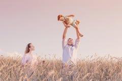 Famille heureuse dans le domaine de céréale au coucher du soleil Image libre de droits