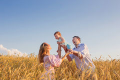 Famille heureuse dans le domaine de céréale au coucher du soleil Photos stock