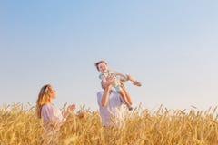 Famille heureuse dans le domaine de céréale au coucher du soleil Photo stock