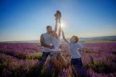 Famille heureuse dans un domaine de lavande sur le coucher du soleil images stock