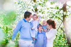 Famille heureuse dans un jardin de floraison de cerisier photographie stock libre de droits