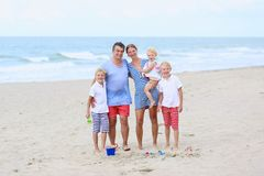 Famille heureuse de 5 ayant l'amusement sur la plage Images stock