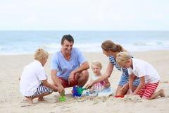 Famille heureuse de 5 ayant l'amusement sur la plage Image stock