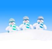 Famille heureuse de bonhommes de neige d'hiver contre le ciel bleu Photo stock