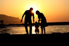 Famille heureuse de la silhouette trois de jeu Photos libres de droits