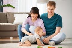 Famille heureuse de métis avec le fils de bébé à la maison photographie stock