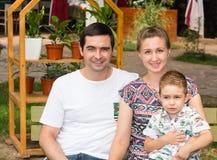 Famille heureuse de père, de mère et d'enfant dans extérieur un jour d'été Parents et enfant de portrait sur la nature Émotions h Images stock