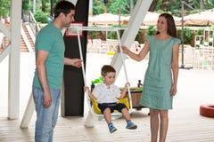 Famille heureuse de père, de mère et d'enfant dans extérieur un jour d'été Parents et enfant de portrait sur la nature Émotions h Photos stock