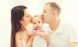 Famille heureuse de plan rapproché de portrait, père de mère embrassant le bébé Image stock