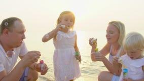 Famille heureuse de quatre bulles de savon jouantes d'esprit extérieures sur la plage pendant le temps de vacances heureux de bea banque de vidéos