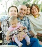 Famille heureuse de trois générations se reposant au parc Image stock