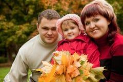 Famille heureuse des personnes de trois en stationnement d'automne Image stock