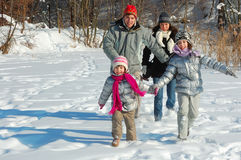 Famille heureuse en hiver, ayant l'amusement avec la neige dehors Image stock