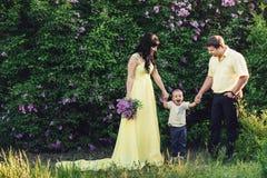 Famille heureuse en parc avec le lilas de floraison Promenade heureuse de maman, de papa et de bébé au coucher du soleil Concept  Photographie stock
