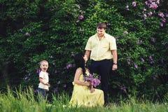 Famille heureuse en parc avec le lilas de floraison Promenade heureuse de maman, de papa et de fils au coucher du soleil Concept  Image stock
