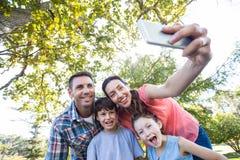 Famille heureuse en parc prenant le selfie Photographie stock libre de droits