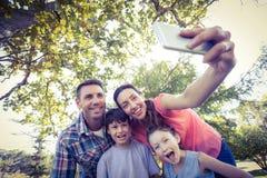 Famille heureuse en parc prenant le selfie Photos stock