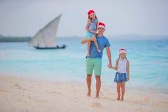 Famille heureuse en Santa Hats des vacances d'été Les vacances de Noël avec la jeune famille de quatre appréciant leur mer se déc Photo stock