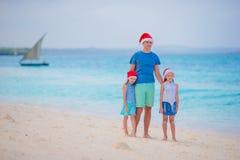 Famille heureuse en Santa Hats des vacances d'été Les vacances de Noël avec la jeune famille de quatre appréciant leur mer se déc Images libres de droits