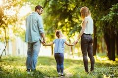 Famille heureuse en stationnement Promenade heureuse de maman, de papa et de bébé au coucher du soleil Le concept d'une famille h Photo libre de droits