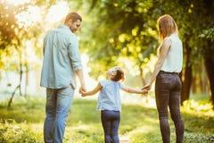 Famille heureuse en stationnement Promenade heureuse de maman, de papa et de bébé au coucher du soleil Le concept d'une famille h Photographie stock libre de droits