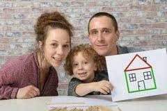 Famille heureuse, enfant jugeant de papier avec la maison de dessin Photo libre de droits