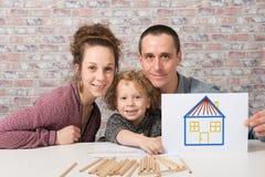 Famille heureuse, enfant jugeant de papier avec la maison de dessin Photo stock