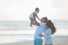 Famille heureuse et bébé appréciant le coucher du soleil dans les loisirs d'été Photographie stock libre de droits